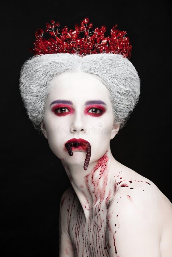 Mysteriöses Schönheitsporträt der Schneekönigin bedeckt mit Blut Helles Luxusmake-up Geleewürmer im Mund stockfotografie