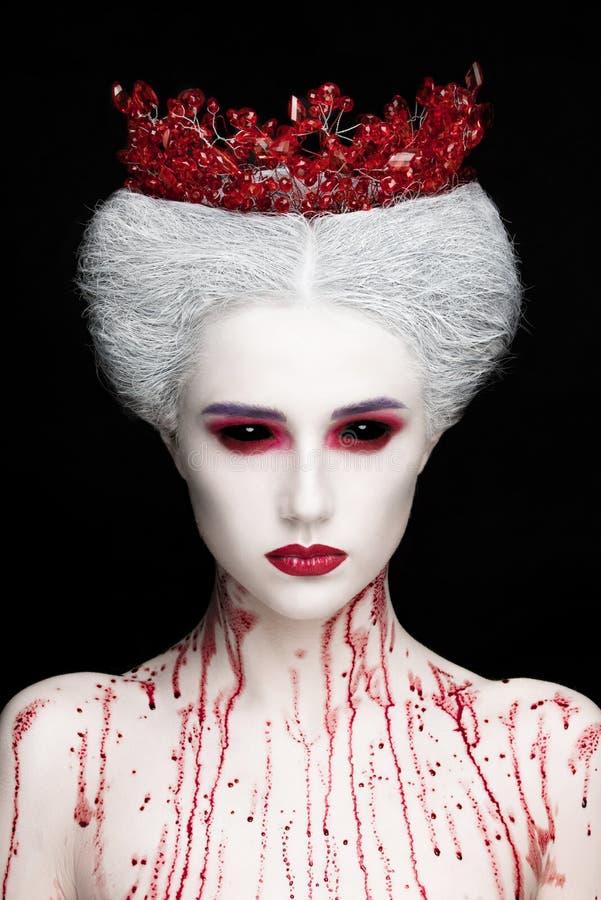 Mysteriöses Schönheitsporträt der Schneekönigin bedeckt mit Blut Helles Luxusmake-up Schwarze Dämonaugen stockfotos
