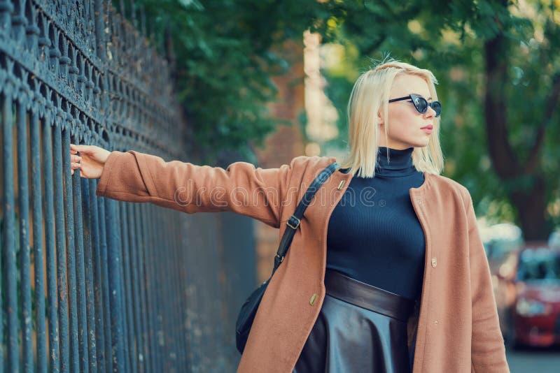 Mysteriöses stilvolles blondes Mädchen geht durch die europäische Metropole und hält den alten Zaun Porträt der jungen Frau herei lizenzfreie stockfotos