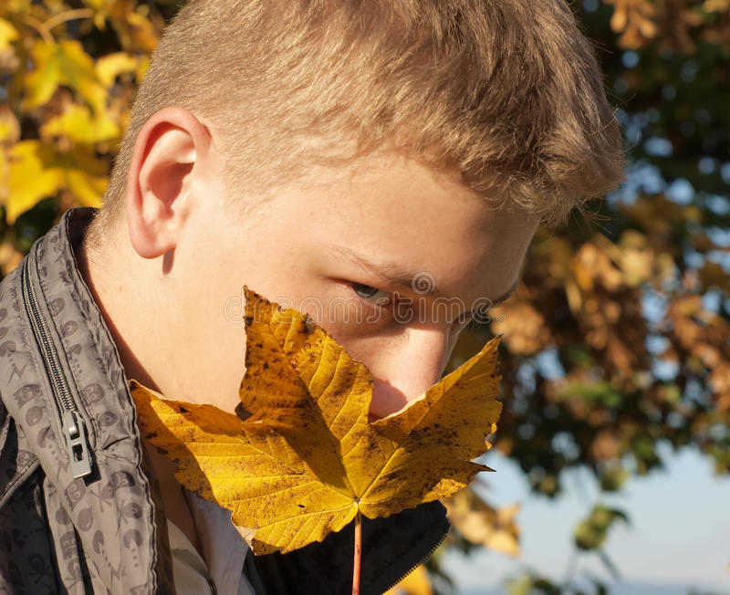 Mysterious autumn. (fall) portrait of young blonde man (teen) (blue eyed) wearing white shirt and grey jacket royalty free stock image