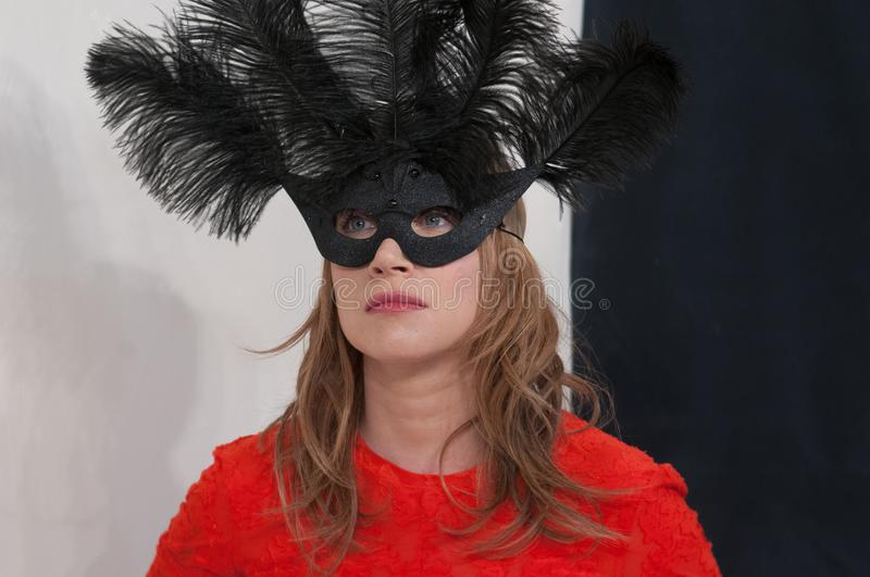 Mysterious beautiful blonde girl in a black mask with feathers in the studio. Girl in red lace t-shirt with big black mask with feathers on her face stock photos