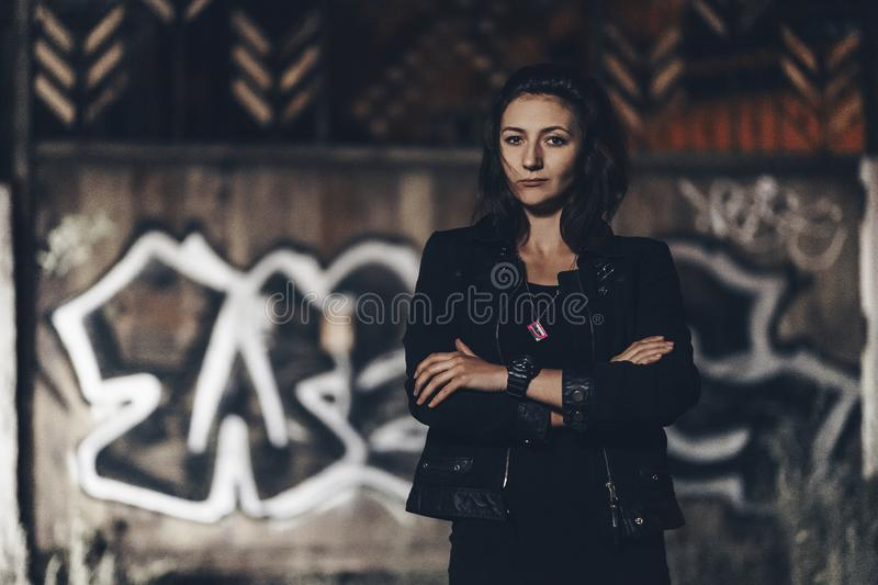 Mysterious beautiful woman in black bodysuit and leather jacket with henna tattoo on her legs sitting on old stone steps with royalty free stock image
