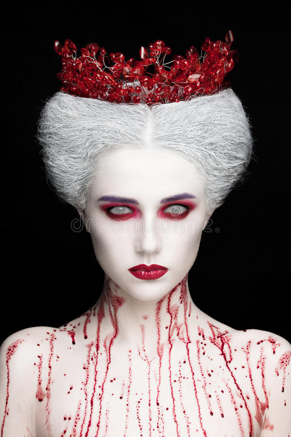 Mysterious beauty portrait of snow queen covered with blood. Bright luxury makeup. White demon eyes. stock photos