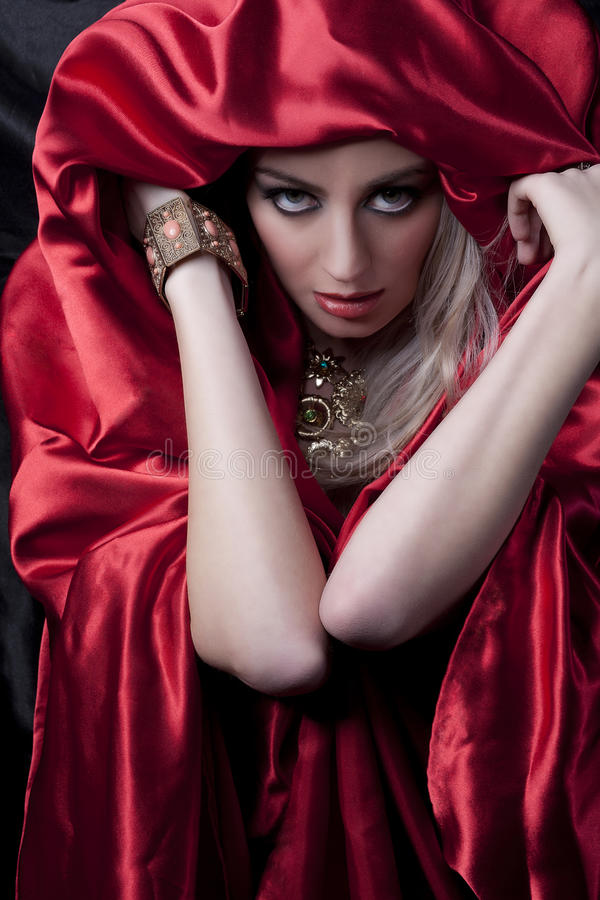 Mysterious blonde in red satin. Glamour portrait of model with red satin sheet cover royalty free stock photos