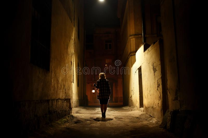Mysterious blonde woman in elegant retro coat with old oil lantern walking in old French street in royalty free stock photos