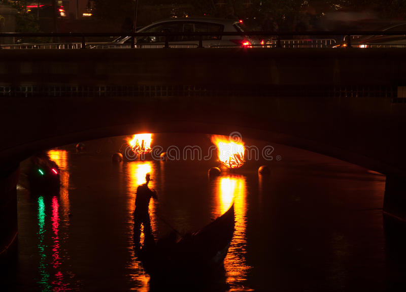 Mysterious Boatman. Nighttime image of a boatman silhouetted by braziers on the river -- Water Fire celebration in Providence, Rhode Island stock photography