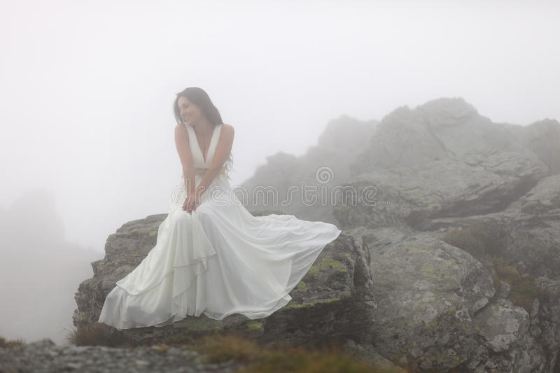Mysterious bride sitting on rocky mountain top. Mysterious young woman in white dress sitting on stones on mountain top surrounded by fog royalty free stock photo