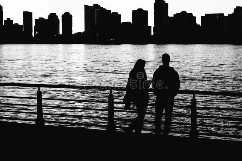 Mysterious couple stands in the the light of the setting sun stock photography