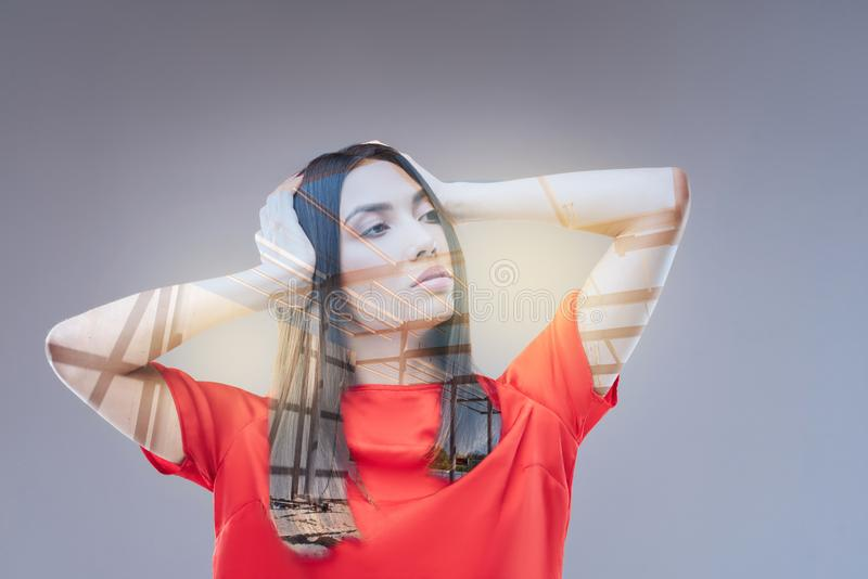 Mysterious cute woman imagining her prospects. Too many ideas. Vulnerable thoughtful young woman standing on the isolated background and touching head while royalty free stock images