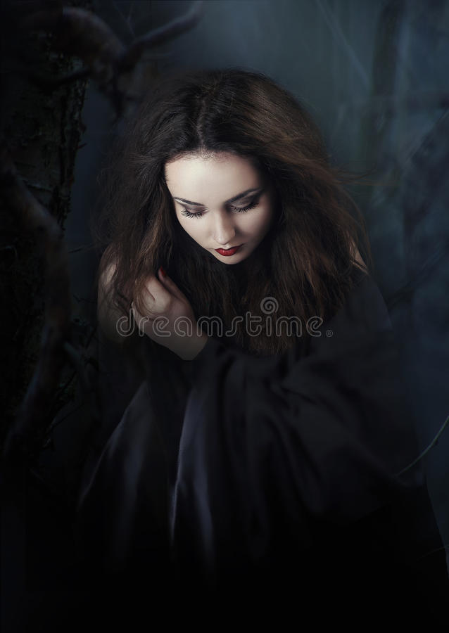 Mysterious dark woman in forest at night. Book cover stock photos