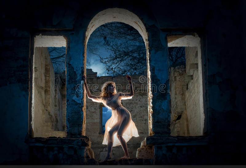 Mysterious female figure. Mysterious female silhouette in the arc of the ruined building royalty free stock photography
