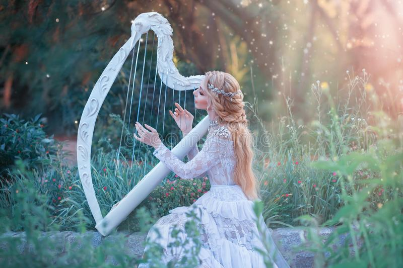 Mysterious forest nymph plays on white harp in fabulous place, girl with long blond hair and elegant lace vintage dress royalty free stock image