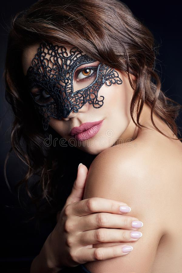Mysterious girl in a black mask, masquerade. Nude brunette. Woman with curly hair on a black background in the mask on the face stock images