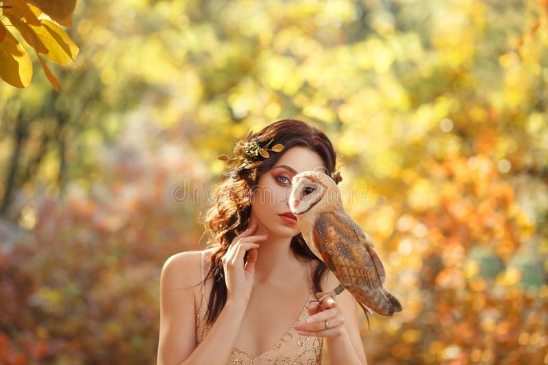 Mysterious girl hides part of face behind owl sitting on the finger of a dark-haired attractive lady, princess dressed. In beige light elegant dress, bright stock images