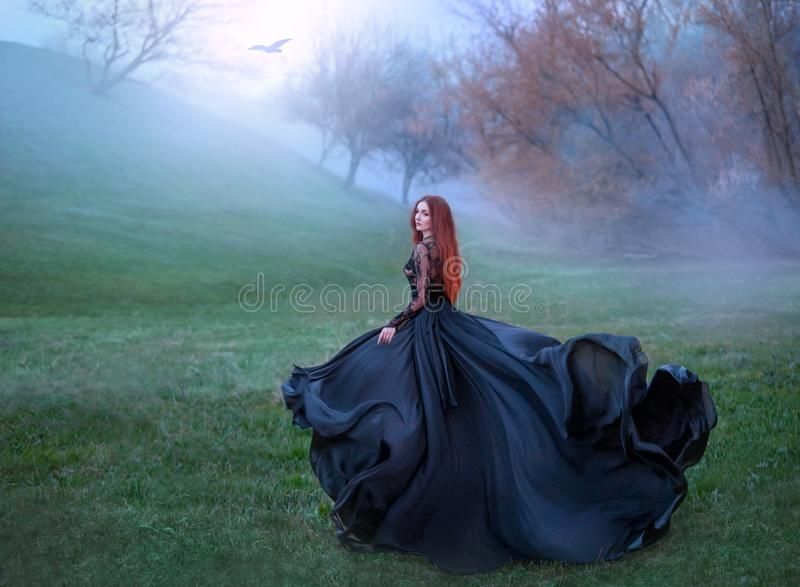 Mysterious girl with red hair runs from forest in gorgeous lace royal dress with flying light long train, lady in green. Frozen meadow and fog, sorceress turns stock image