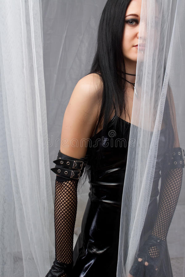 Mysterious gothic girl. Gothic beautiful woman behind a curtain stock photo