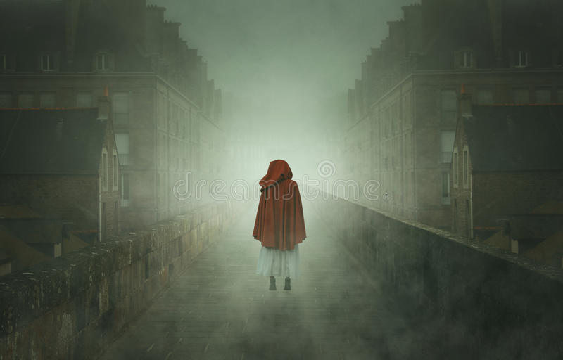 Mysterious hooded woman in a stone city stock photos