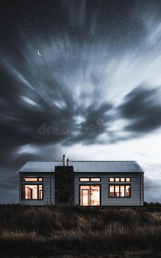 A mysterious house with the lights on  in a dark field stock photo