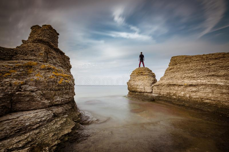 Mysterious human being standing on the rock stock image