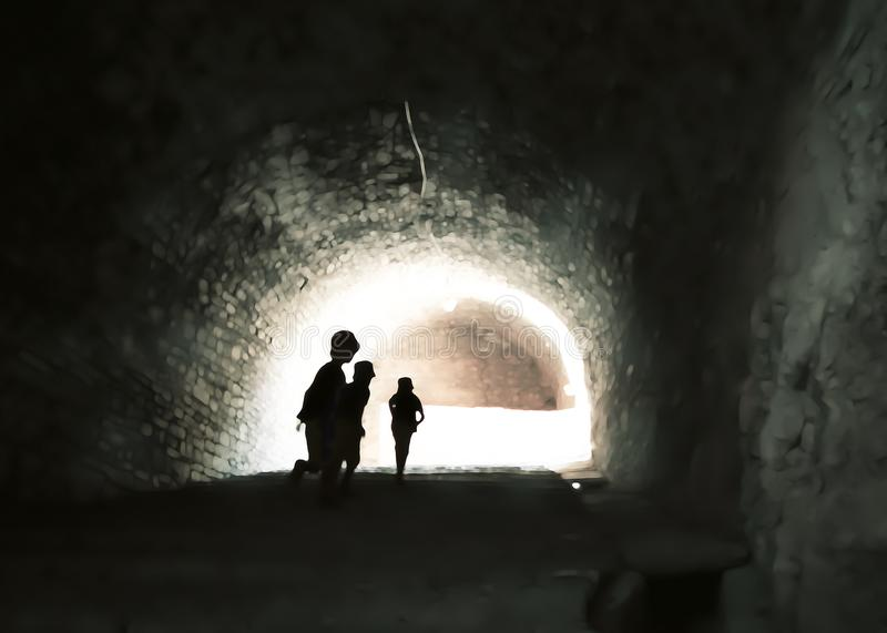 Mysterious image of ghostlike children in an obscure cave. Mysterious image of silhouetted children running towards the opening of a gloomy grotto vault stock image
