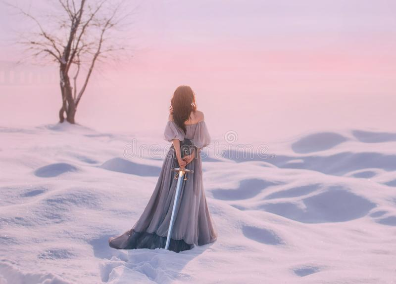Mysterious lady from Middle Ages with dark hair in gentle gray blue dress in snowy desert with open back and shoulders. Sharp sword behind, model stands back stock photo