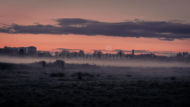 Mysterious landscape of mist on field at dusk in spring royalty free stock photo