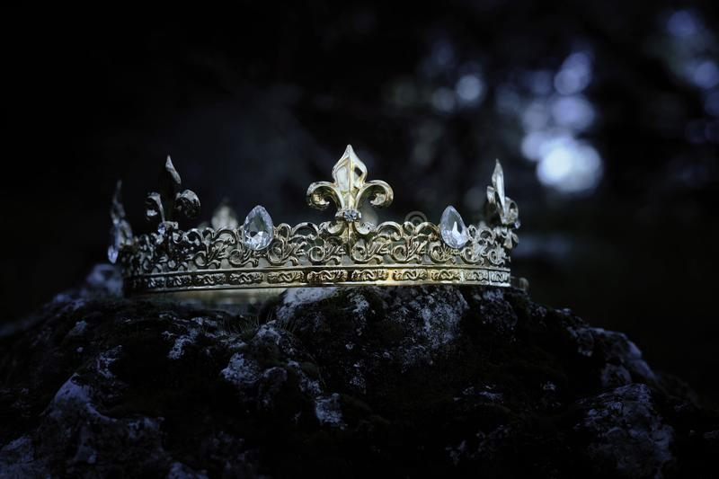 Mysterious and magical photo of gold king crown over the stone covered with moss in the England woods or field landscape with royalty free stock photos