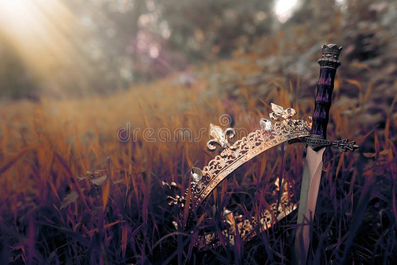 Mysterious and magical photo of gold king crown and sword in the England woods or field landscape with light flare. Medieval. Period concept stock photo