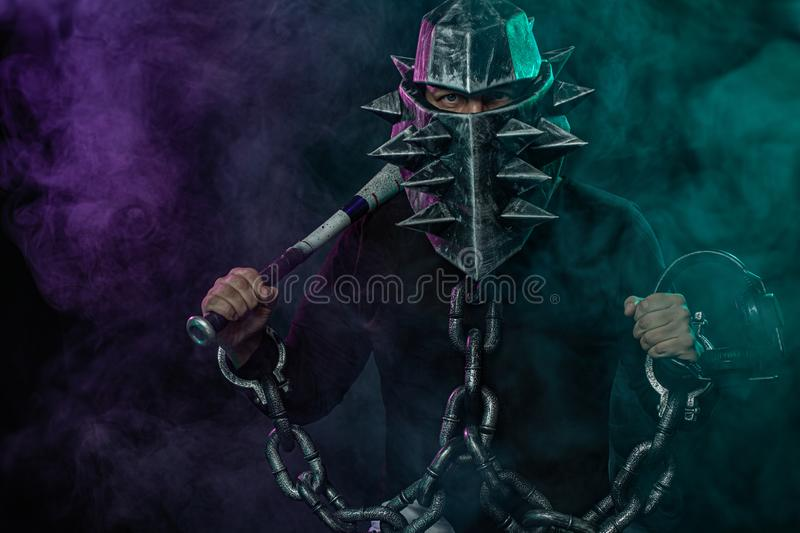 Mysterious man in a helmet with a bat and chains in black wear. Fantasy book or computer game cover concept on halloween. Mysterious Man in Black Hoodie. Sexy royalty free stock photos