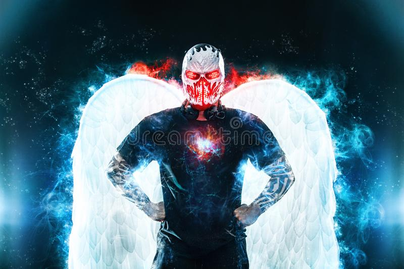 Mysterious man in black wear and skull mask with white wings. Fantasy book or computer game cover concept on halloween. Mysterious Man in Black Hoodie. Sexy Hero royalty free stock image