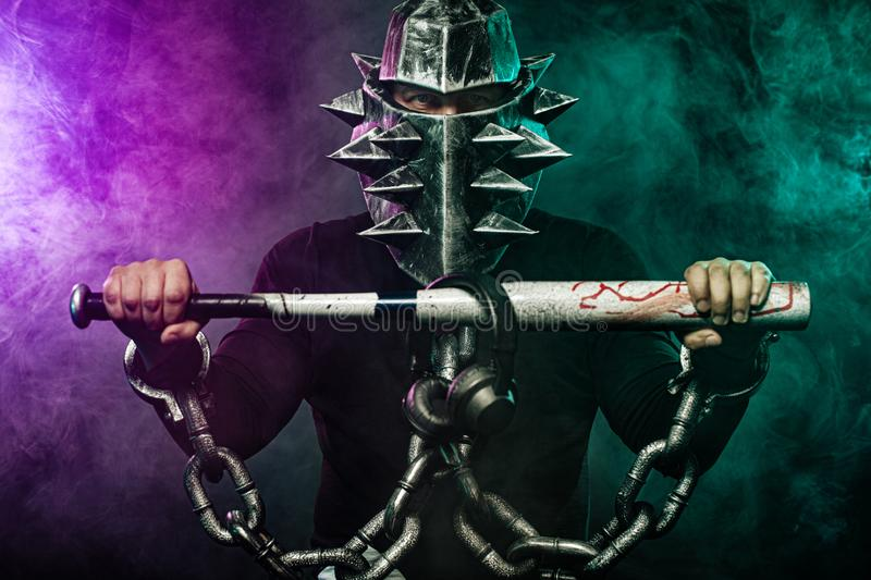 Mysterious man in a helmet with a bat and chains in black wear. Fantasy book or computer game cover concept on halloween. Mysterious Man in Black Hoodie. Sexy stock images