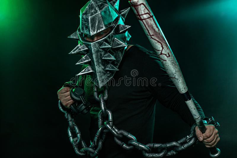 Mysterious man in a helmet with a bat and chains in black wear. Fantasy book or computer game cover concept on halloween. Mysterious Man in Black Hoodie. Sexy stock image