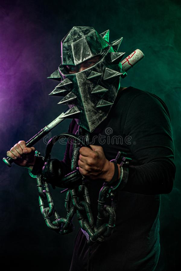 Mysterious man in a helmet with a bat and chains in black wear. Fantasy book or computer game cover concept on halloween. Mysterious Man in Black Hoodie. Sexy royalty free stock photography