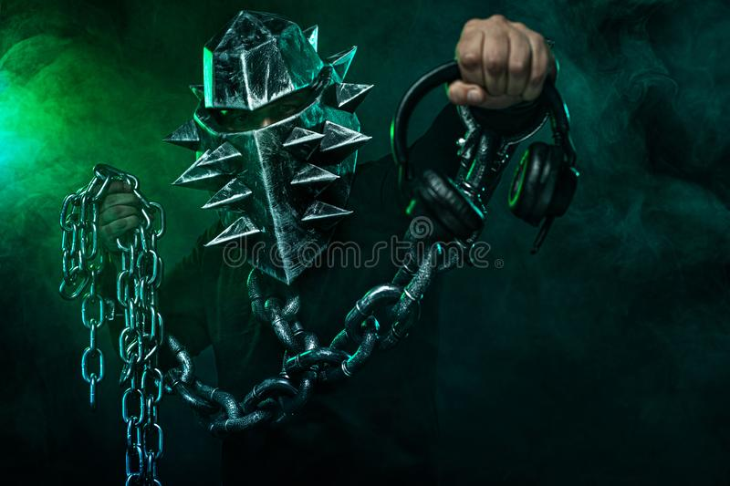 Mysterious man in a helmet with a bat and chains in black wear. Fantasy book or computer game cover concept on halloween. Mysterious Man in Black Hoodie. Sexy royalty free stock photo