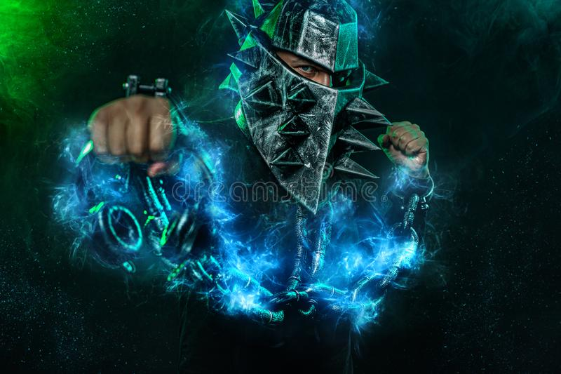 Mysterious man in a helmet with a bat and chains in black wear. Fantasy book or computer game cover concept on halloween. Mysterious Man in Black Hoodie. Sexy stock photography