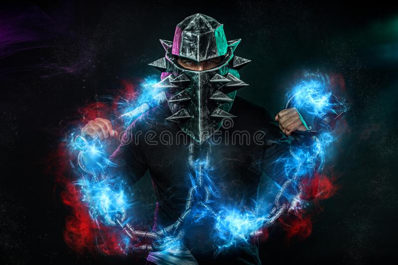 Mysterious man in a helmet with a bat and chains in black wear. Fantasy book or computer game cover concept on halloween. Mysterious Man in Black Hoodie. Sexy royalty free stock images