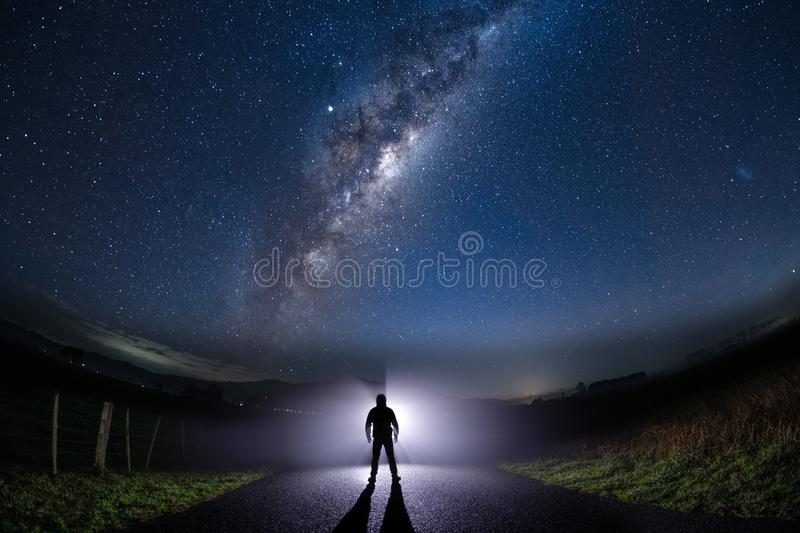 Mysterious man standing in the middle of the road looking into bright light with milky way starry night sky royalty free stock images