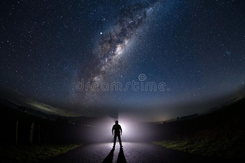 A mysterious man standing in the middle of the road looking into bright light with milky way starry night sky royalty free stock photo