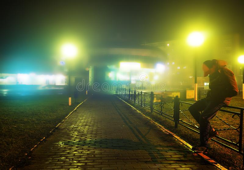 A mysterious man stands alone in the street, among cars in an empty city, walks the night street, dreams stock photography