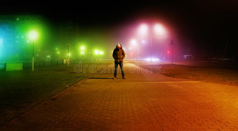 A mysterious man stands alone in the street, among cars in an empty city, walks the night street, dreams. A mysterious man stands alone in the street, among cars stock photo