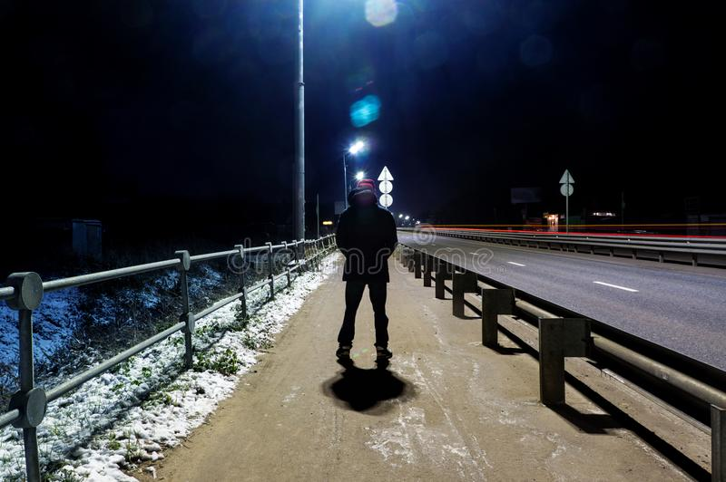 a mysterious man stands alone in the street, among cars in an empty city, weat road after the rain, walks the night street, dreams royalty free stock photography