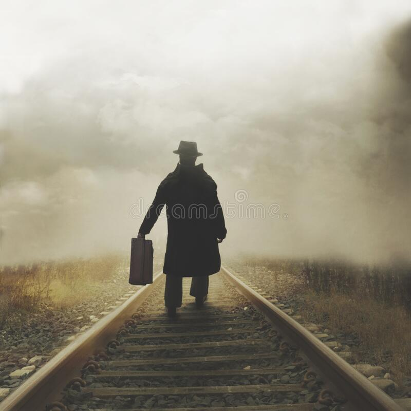 Free Mysterious Man Walks With His Suitcase On The Tracks Towards An Unknown Destination Royalty Free Stock Photo - 195689945