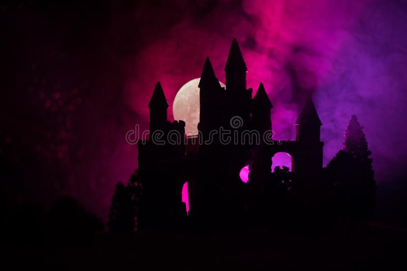 Mysterious medieval castle in a misty full moon. Abandoned gothic style old castle at night royalty free stock photography