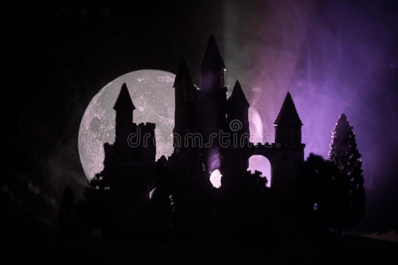 Mysterious medieval castle in a misty full moon. Abandoned gothic style old castle at night stock photo
