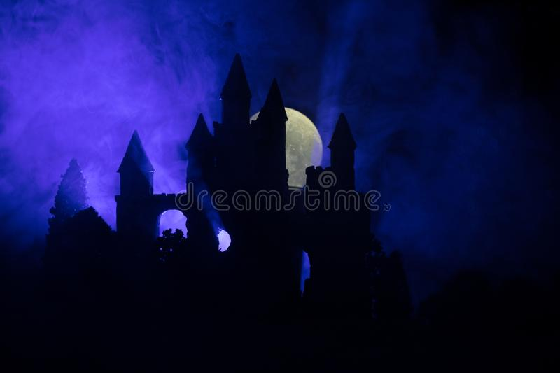 Mysterious medieval castle in a misty full moon. Abandoned gothic style old castle at night stock image
