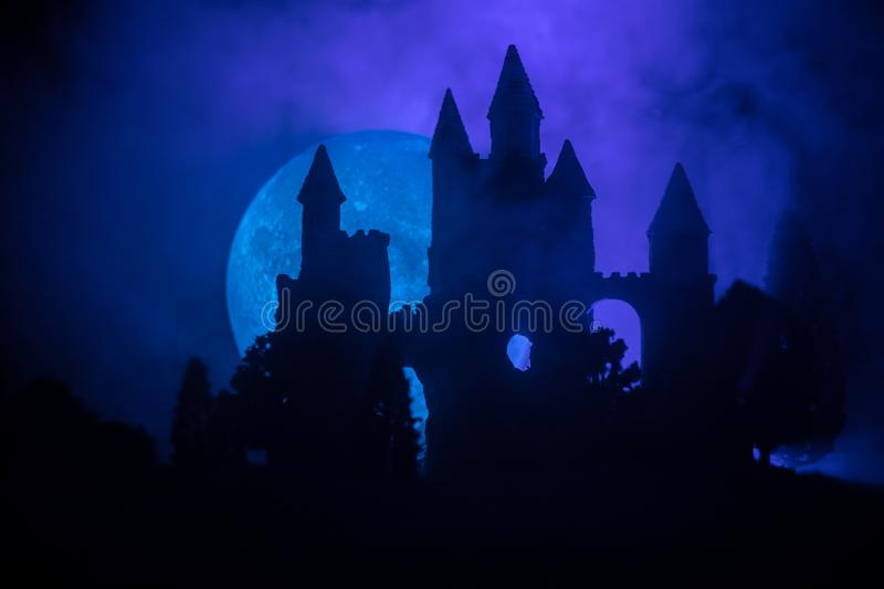 Mysterious medieval castle in a misty full moon. Abandoned gothic style old castle at night stock photography