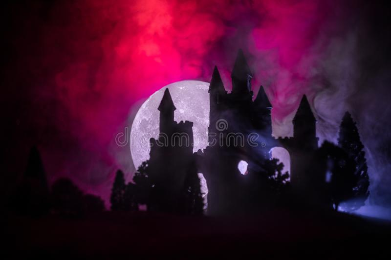 Mysterious medieval castle in a misty full moon. Abandoned gothic style old castle at night royalty free stock photo