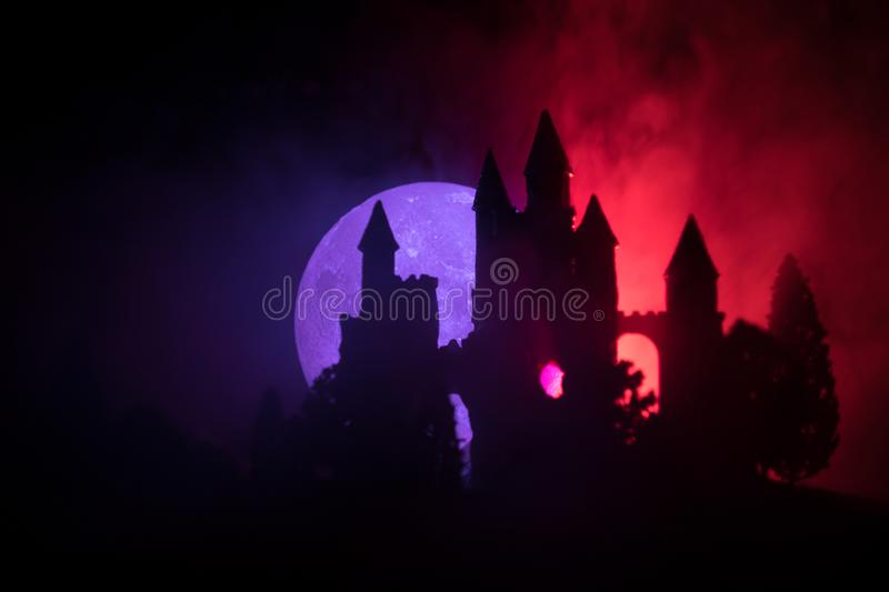 Mysterious medieval castle in a misty full moon. Abandoned gothic style old castle at night royalty free stock image