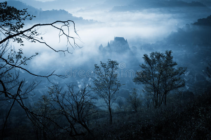 Mysterious misty morning over Biertan village, Transylvania, Romania. Blue colors. Halloween postcard concept stock photography