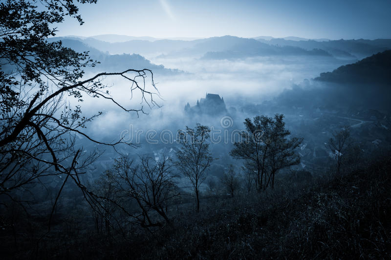Mysterious misty morning over Biertan village, Transylvania, Romania. Blue colors. Halloween postcard concept royalty free stock image
